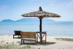 Bench and sunshade umbrella on the beach Stock Photos