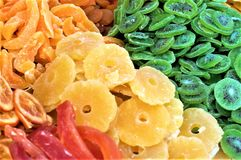 Dried fruit in a market stall. Orange, banana and colorful kiwis. Bench sweets at the market stock image