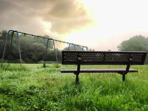 Bench and swing set frame. In an abandoned playground royalty free stock images