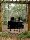 Bench Swing for Two in Backyard Setting. Two people enjoying Southern living and watching for alligators on  a backyard bench swing with view of river and Royalty Free Stock Image
