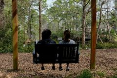 Bench Swing for Two in Backyard Setting. Two people enjoying Southern living and watching for alligators on  a backyard bench swing with view of river and Stock Images