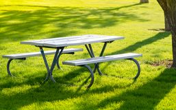 Bench and table in the public park on the green meadow on a sunny day. Great for many people for the birthday party and. Bench and tabl in the public park on the royalty free stock image