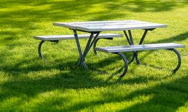 Bench and table in the public park on the green meadow on a sunny day. Great for many people for the birthday party and. Bench and tabl in the public park on the royalty free stock images