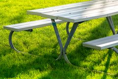 Bench and table in the public park on the green meadow on a sunny day. Great for many people for the birthday party and. Celebrations stock photography