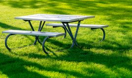 Bench and table in the public park on the green meadow on a sunny day. Great for many people for the birthday party and. Bench and tabl in the public park on the royalty free stock photography