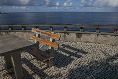 A bench and a table by the seaside, Madeira, Portugal. Royalty Free Stock Image