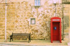 Bench and telephone booth at Xewkija, Gozo. Bench and telephone booth in the tiny village of Xewkija pronounced `showkeeya` on the island of Gozo against a stock photo