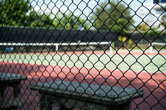 Bench beside the tennis court. Looking through the iron fence Stock Images