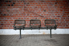 Bench with three seats in front of a brick wall Royalty Free Stock Images