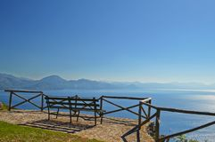 A bench overlooking the Gulf of Policastro, in Italy. A bench to admire an enchanting landscape of sky and sea royalty free stock photo