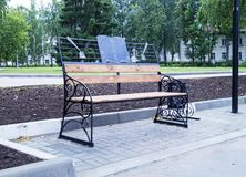 Bench in town park. For rest passer-by on background of the buildings and green tree Royalty Free Stock Image