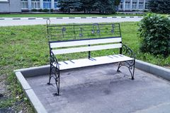 Bench in town park. For rest passer-by on background of the buildings and green tree Stock Photography