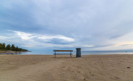 Bench and Trash Can on Beach by Ocean Royalty Free Stock Image