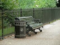 Bench and trash can in park Stock Photo