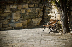 Bench, tree and old stone wall Royalty Free Stock Image