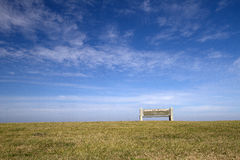 Wooden bench under blue sky Stock Images