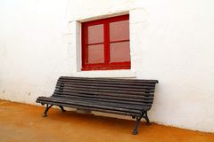 A bench under a red window Stock Image