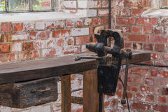 Bench vice installed on a workbench. Old black bench vice installed on a workbench Royalty Free Stock Images