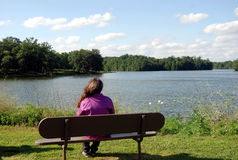Bench with a view. Girl sitting on park bench looking at the lake Stock Images