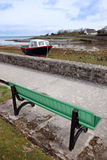 Bench view of old fishing boat moored Stock Image