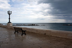 A bench with view on the sea. In a  rainy day in Bari, Italy Stock Photography