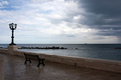A bench with the view on the sea. A bench with view on the sea in a  rainy day in Bari, Italy Royalty Free Stock Images