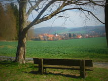 Bench with a view of spring countryside. Bench under a tree with a village in the background shooted in West Bohemia, Czech Republic. The photo was taken on Royalty Free Stock Images