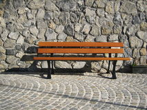 A bench waiting for you. A light brown bench against a grey walll in a french village stock photography