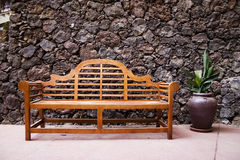 Bench on wall. Bench with a stone wall on back Royalty Free Stock Image