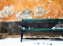 Bench and wall. Green bench in snow against decaying stucco wall Royalty Free Stock Images