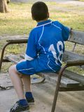 Bench-warmer. Boy in football uniform sitting on the bench Royalty Free Stock Photo