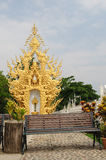 Bench at Wat Rong Khun, Chiang Rai, Thailand. Bench with golden sculpture background Royalty Free Stock Photos