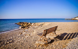 Bench by the water. Aegean sea, Greece Royalty Free Stock Photo