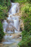 Bench at the waterfall Stock Images