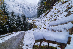 Bench on the way. Snowy bench on the way in mountains Royalty Free Stock Photo