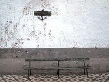 Bench by White Wall with Sign Royalty Free Stock Photography
