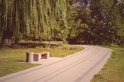 A bench and a winding road. Toned royalty free stock photo