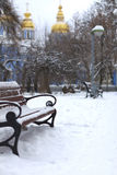 Bench in the winter against Christian church Stock Image