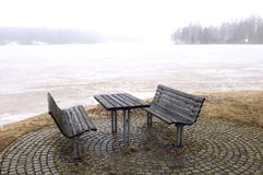 Bench in winter at the shore Royalty Free Stock Photo