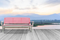 Bench on wooden foothpath. Along the lake with mountain against sunset behind Stock Photos