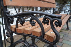 Bench. Wooden bench with wrought iron handrails royalty free stock photo