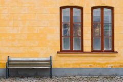 Bench and yellow wall. With two windous stock photo
