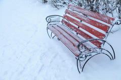 Benche i vinter parkerar, snönedgångar som är utomhus- Arkivbild
