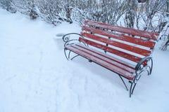 Benche i vinter parkerar, snönedgångar som är utomhus- Arkivfoton