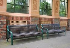 Benches. Two empty benches made of wood and metal against brick building stock photo