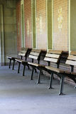 Benches. Four benches in a row in front of the wall Royalty Free Stock Image