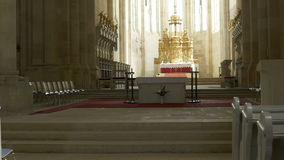 Benches and Altar in Church. Golden altar and wooden benches, in the rays of light, in a catholic medieval church stock video footage