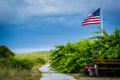Benches and American flag along a walkway to the beach in Seabro Royalty Free Stock Photo