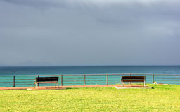 Benches on cliff with sea and stormy clouds Stock Photos