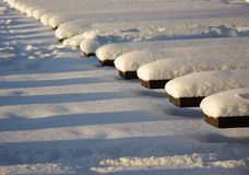 Benches Covered with Snow. Many benches covered with white snow. Shadows as stripes on snow Royalty Free Stock Photography